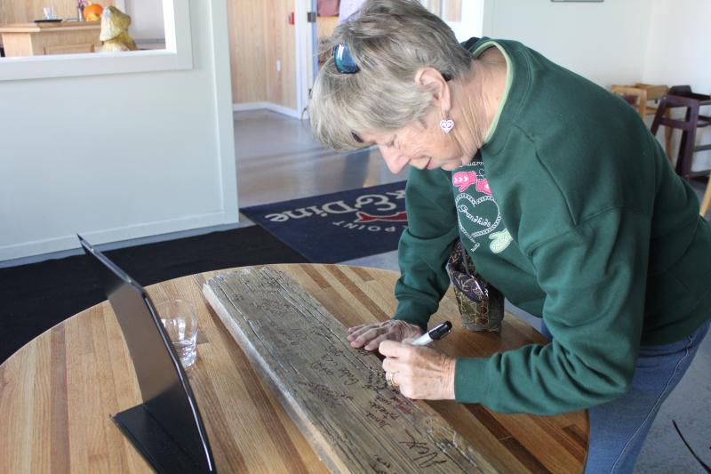 A Dock & Dine customer signs a dock plank which will be hung inside the new facility.