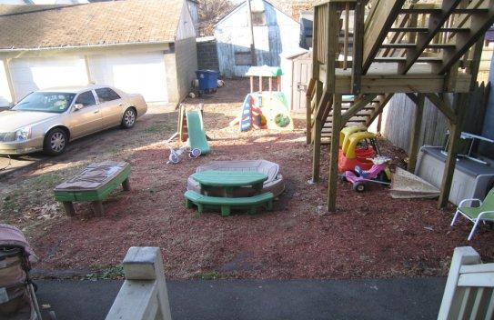 A children's outdoor play area without a fence or protective barrier to prevent children from entering the driveway where cars are parked. Also shown is a set of stairs without protective gates.
