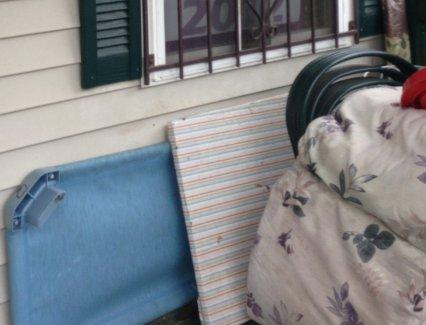 Children's sleeping cots stored outside on a front porch.