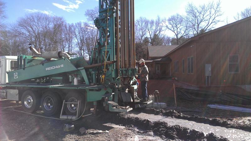 Workers drill a hole into the ground in advance of installing geothermal piping. Geothermal technology uses ambient ground temperatures to heat and cool buildings.