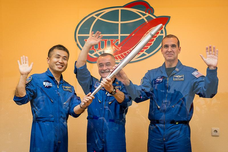 Expedition 38 Flight Engineer Koichi Wakata of the Japan Aerospace Exploration Agency, left, Soyuz Commander Mikhail Tyurin of Roscosmos, and, Flight Engineer Rick Mastracchio of NASA, right, smile and was as they hold an Olympic torch bound for the ISS.