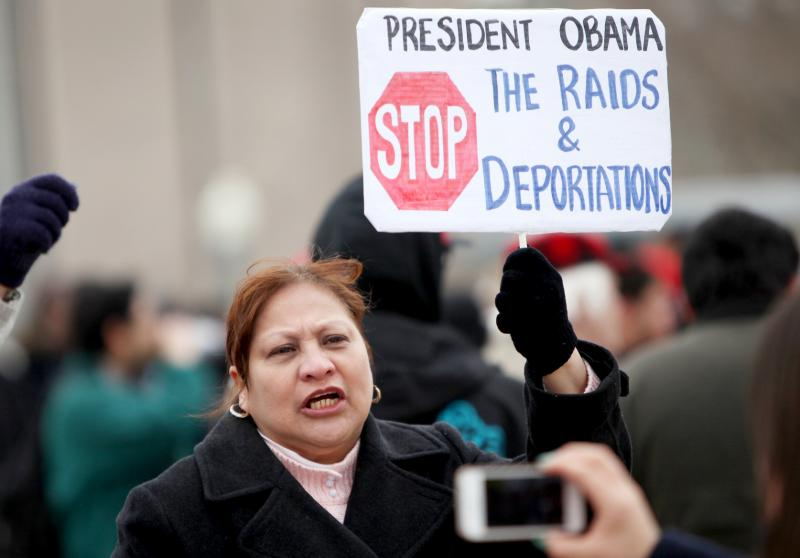 "A woman held a sign saying ""Stop the raids and deportations"" at CCSU during President Obama's visit."