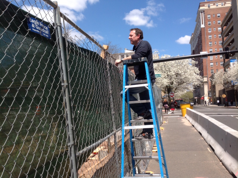 Robert Greenberg has been barred from searching the CenterPlan site. Recently the company put up a green screen on the surrounding fence, so Greenberg watches from a ladder.