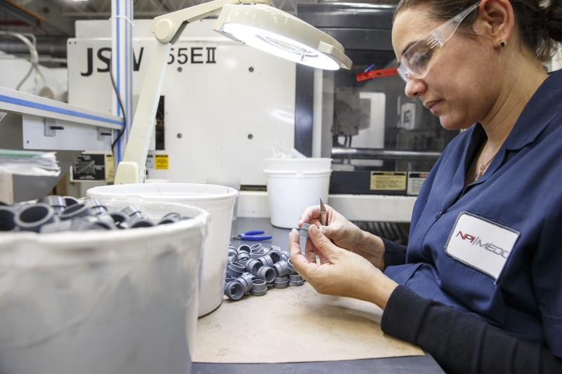 Operator Angela Hernandez performs a trimming operation and visual inspection on a prototype molding process at NPI Medical in Ansonia.