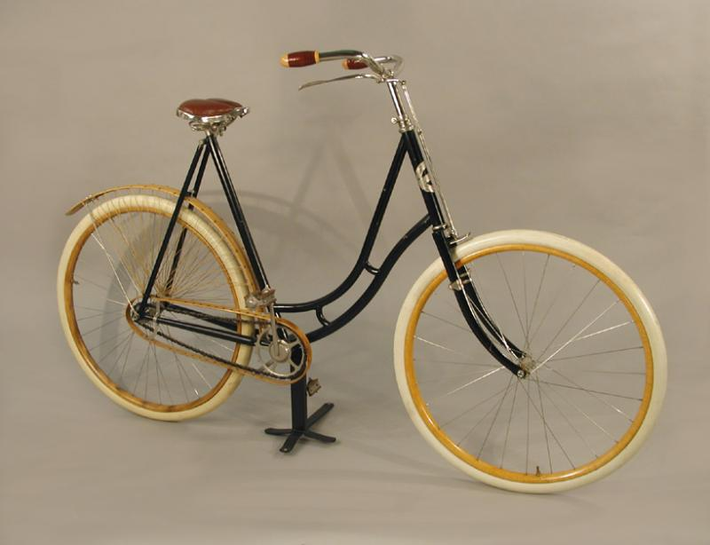 "Woman's Bicycle made by the Pope Manufacturing Company, 1890s. In the mid-1890s Pope introduced safety bicycles for both men and women, the latter featuring a ""drop frame"", rear wheel skirt guard and more comfortable seat."