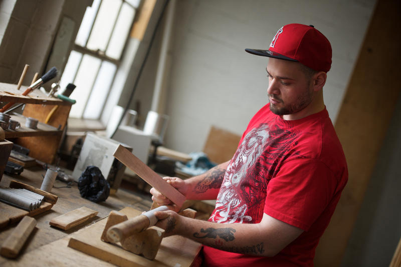 John Rivera removes pipes from the drying cabinet and shapes them on a mandrel.