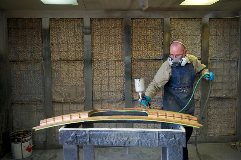 Richard Walker sprays the back of a console toe board in a finishing room at Austin Organs.