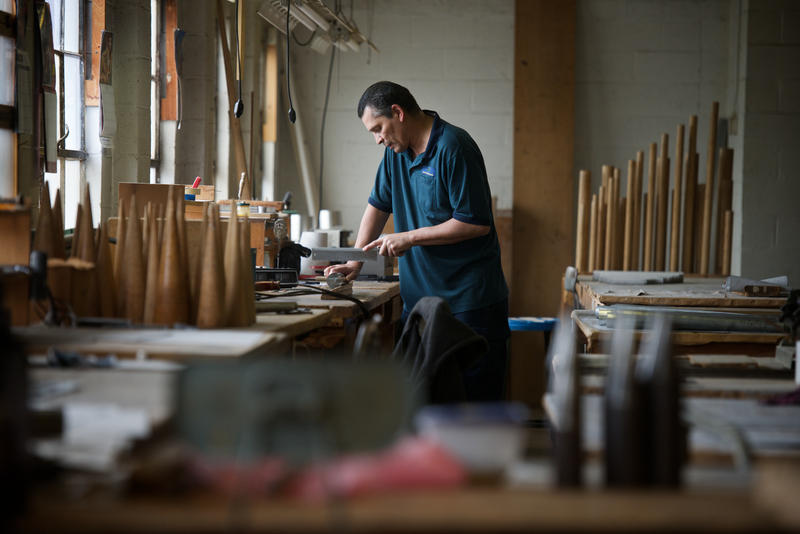 Tony Valdez, a pipe maker at Austin Organs, cuts out the windows for tuners in zinc pipes.