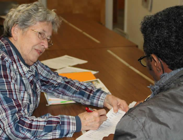 Volunteer Louise Thoman works with a client at IICONN.