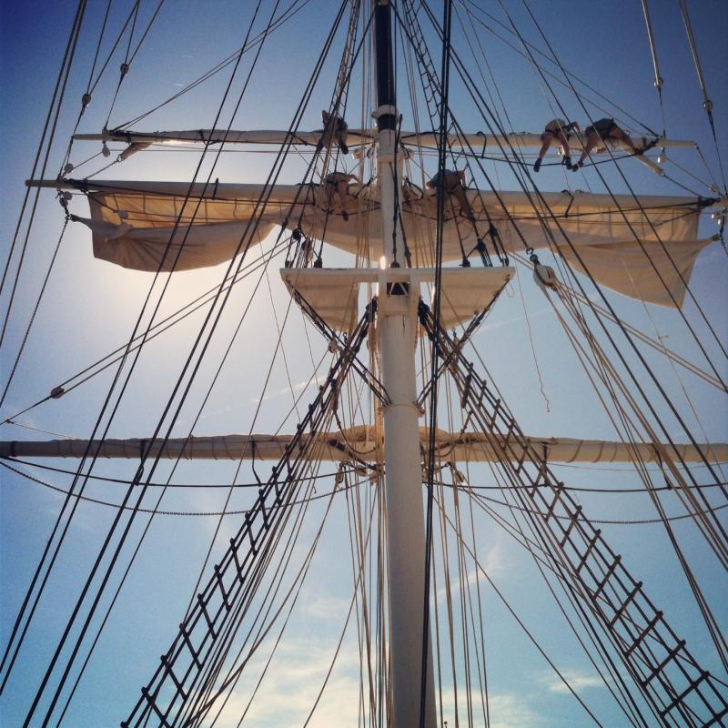 Looking up on board the Charles W. Morgan as the crew furls her fore topsails.