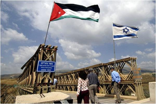 Jordanian and Israeli flags fly above the bridge over the Yarmouk River, the gateway to Peace Island