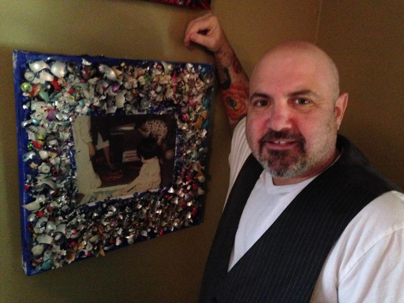 "Tony Ferraiolo next to his artwork, ""A Broken Christmas"""