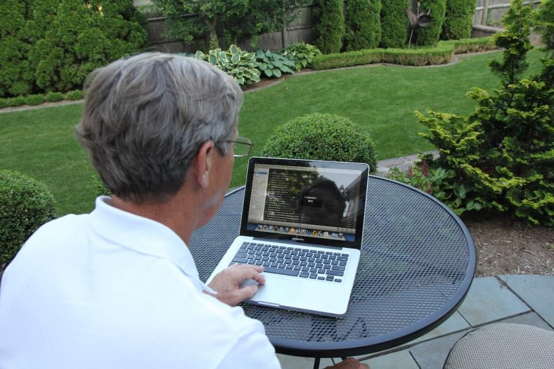 Avery Buell, looking up pictures of his back yard, before it was landscaped in 2007.