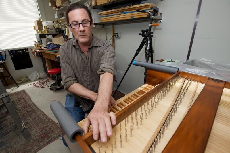 Zuckermann Harpsichords International owner Richard Auber tunes a harpsichord in the finishing room of his Stonington, CT company.