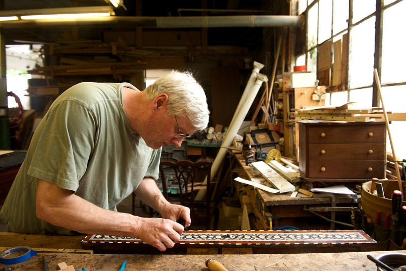 Woodworker Mike Lynch, a restoration specialist, replaces old inlay made of bone and black wood.