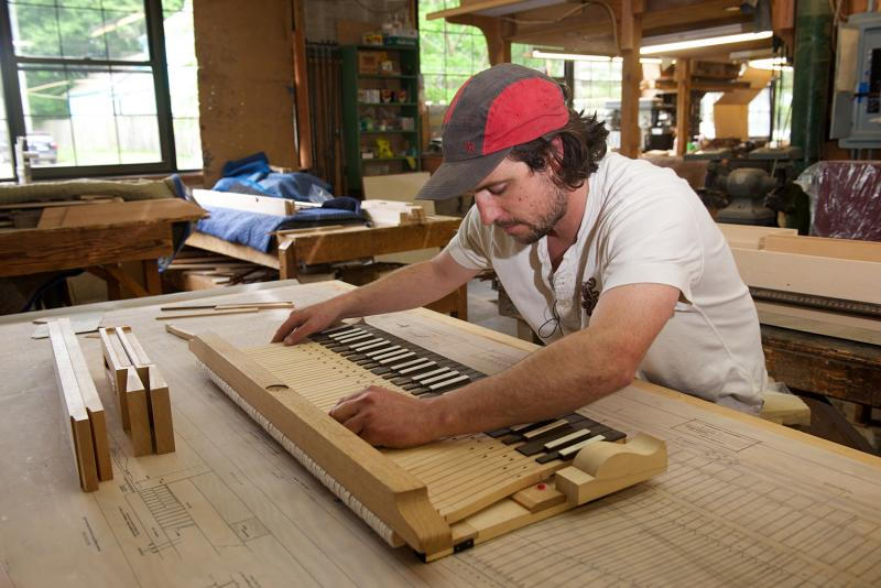 Will Plouffe, a harpsichord builder with Zuckermann Harpsichords International, levels and balances a keyboard he built.