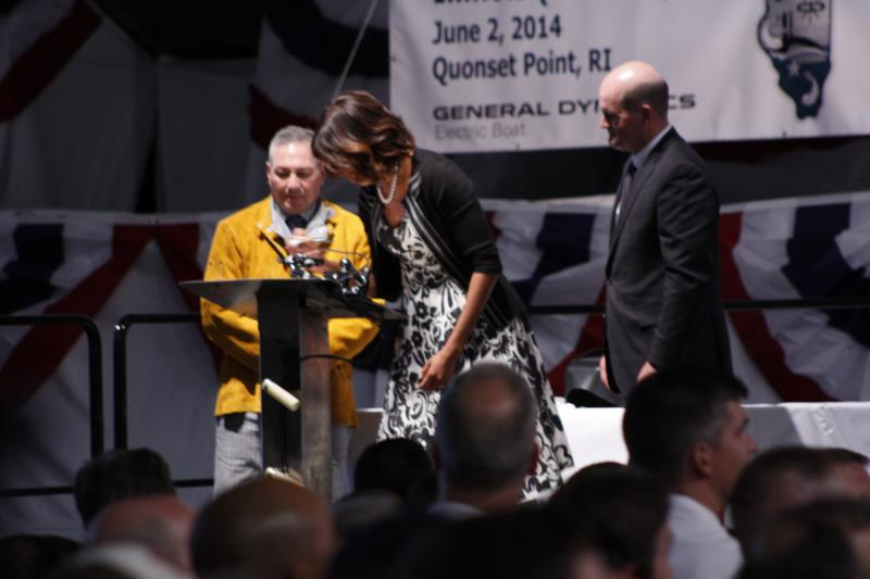 First Lady Michelle Obama signs her initials on a plate that will be mounted on the USS Illinois
