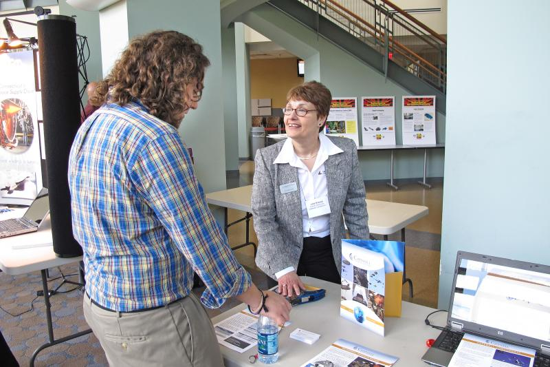 A representative from Capewell Components talks to a potential job candidate at a manufacturing careers fair.