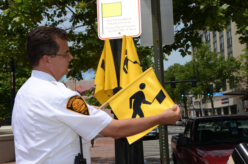 "Bridgeport Police Chief Joseph Gaudett displays one of six ""crosswalk flags"" being piloted at Broad Street in Bridgeport."