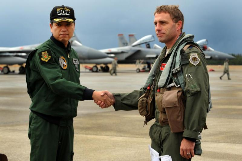 Japanese Air Self Defense Force Lt. Col. Miyake Hideaki, 306th Tactical Fighter Squadron commander, and U.S. Air Force Lt. Col. Morris Fontenot, 67th Fighter Squadron commander, shake hands during a press conference on Komatsu Air Base, Japan, in 2013.