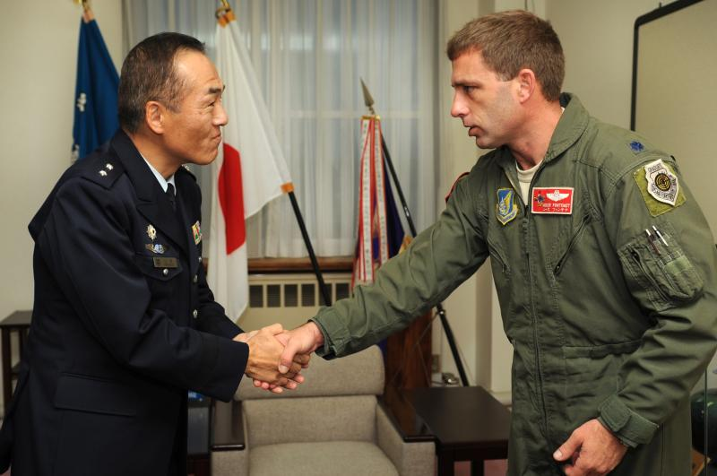 Japanese Air Self Defense Force Maj. Gen. Yuich Yamamoto, Komatsu Air Base and 6th Wing commander, and U.S. Air Force Lt. Col. Morris Fontenot, 67th Fighter Squadron commander, shake hands during a meeting on Komatsu Air Base, Japan, Dec. 12, 2013.