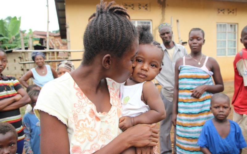 A 19 year old woman fully recovered from Ebola kisses her baby outside a Doctors Without Borders Clinic in Sierra Leone.