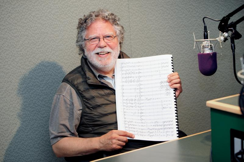 Wesleyan University music professor Neely Bruce hold up the orchestral score of Columbiad, a work inspired by the massive migratory flocks of the now extinct passenger pigeon.