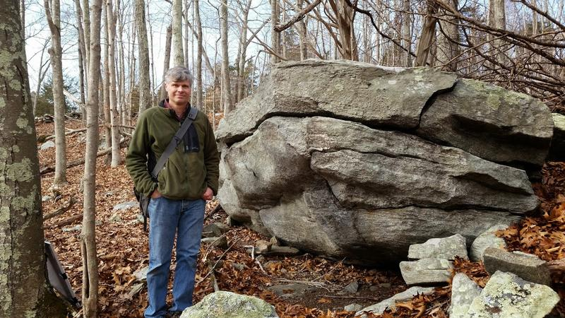 "Wesleyan geologist Phil Resor stands next to a ""granitic gneiss"" rock formation on the southeastern side of the Lake Char fault system."