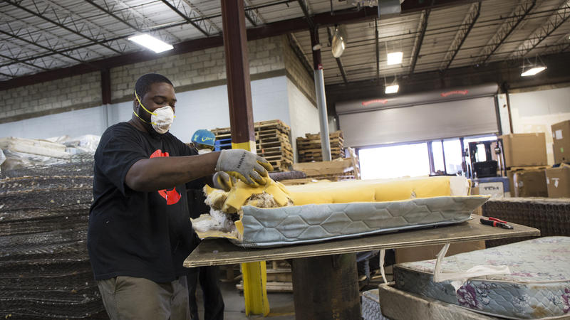 Andre Williams, a worker at Park City Green in Bridgeport, deconstructs a mattress.