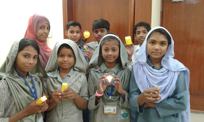 Pakistani girls hold the solar-powered desk lamps they designed with students in America.