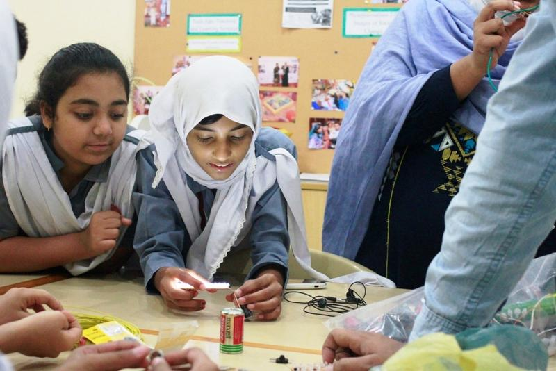 Girls at a school in Pakistan work on their solar-powered light they co-developed with American students.