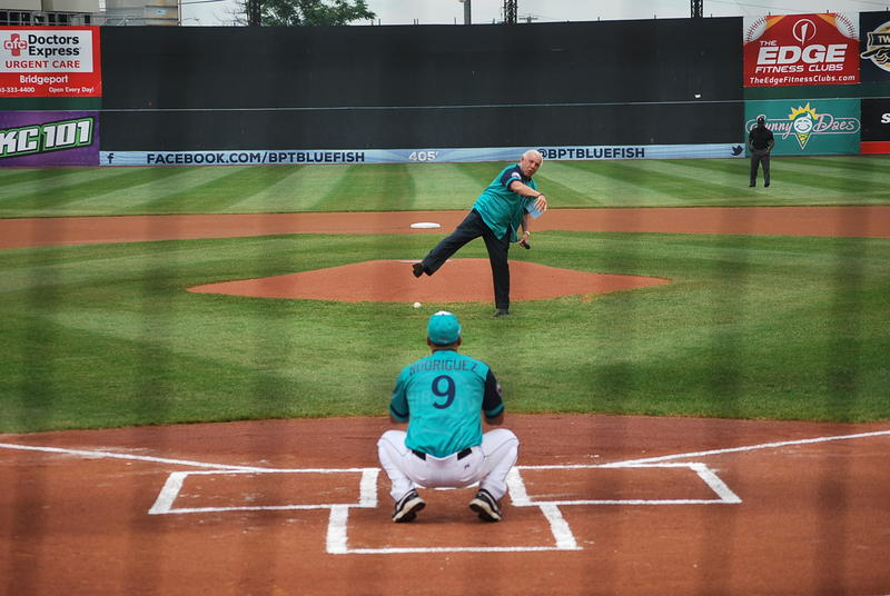 WWE hall-of-famer Ric Flair throws the ceremonial first pitch to Liberty coach (and Bluefish player/coach) Luis Rodriguez.