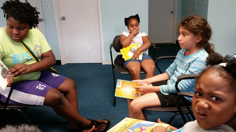 In the foreground, Victoria, five, sneaks a peak at the camera as a RiseUP scholar reads to kids.