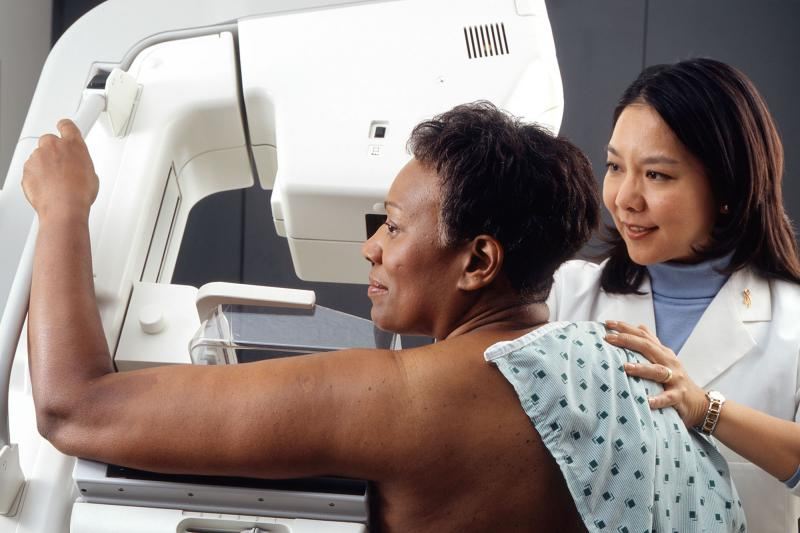 A woman receives a mammogram.