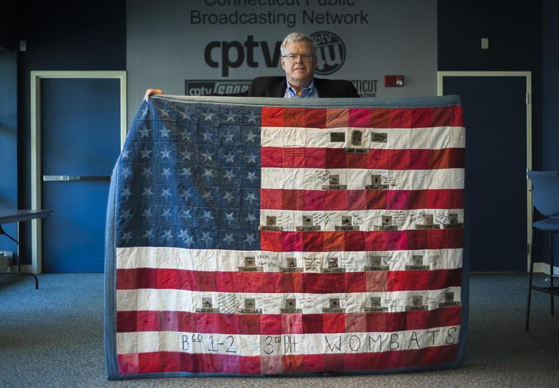 Gil Sanborn has supported Army platoons since 9/11. He is holding a quilt given to him by service members.