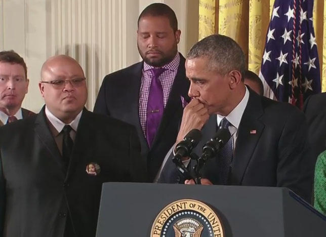 When talking about the Sandy Hook shooting, President Obama teared up. Jimmy Greene, whose daughter Ana was among the Newtown victims, stands behind.