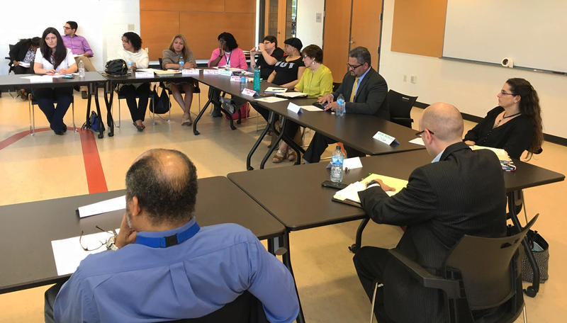 DCF Deputy Commissioner Fernando Muniz (center right) listens at a meeting inside The Parker Memorial Community Center in Hartford.