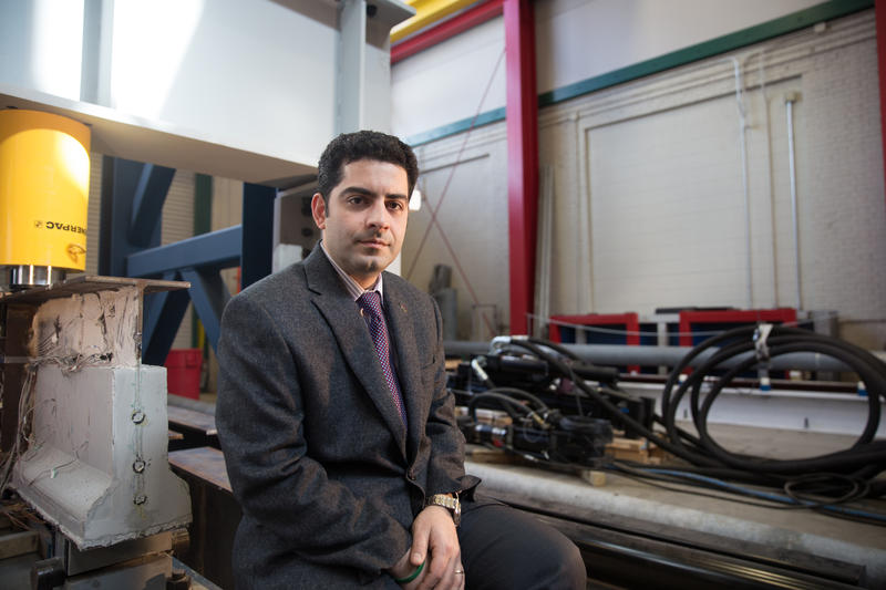 UConn engineering professor Arash Zaghi sits to the right of the concrete cast he's researching that could improve how engineers repair bridges.