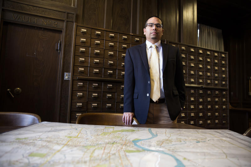 Robert Cotto, Jr.'s old neighborhood in the North End received a poor survey ranking in a system of disinvestment in the first half of the 20th century. Cotto is pictured with a Hartford map in the Connecticut State Library.