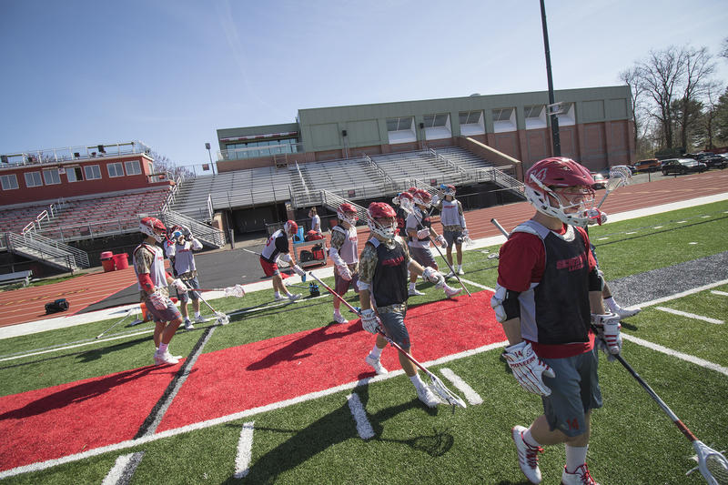 Sacred Heart University men's lacrosse players walk toward the field after a water break during a practice on the school's campus in Fairfield.