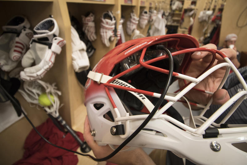 Sacred Heart University men's lacrosse coach Jon Basti holds a player's helmet, with the GForceTracker plugged in to its charging station in the team's locker room.