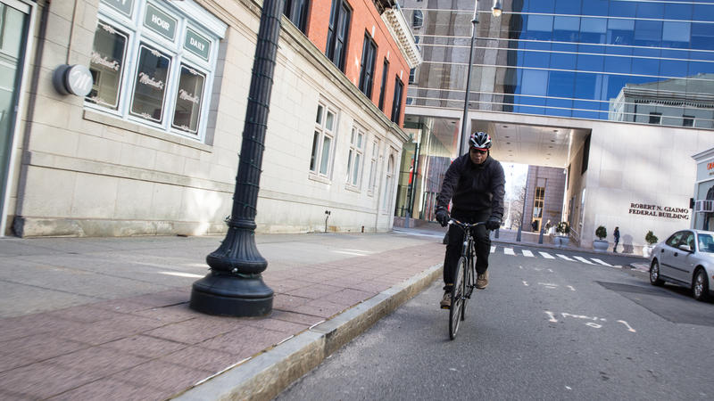 New Haven cycling advocate Johnny Brehon bikes through downtown New Haven. Brehon has been involved in the planning of New Haven's Bike Month, which aims to increase diversity in the cycling community.