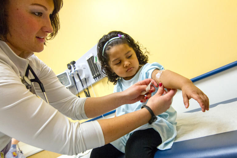 Angely Nunez, 3, watches as Lauren Frazer, a nurse at Connecticut Children's Primary Care Center in Hartford, applies a topical anesthetic to her arm before a blood draw to check for lead levels.