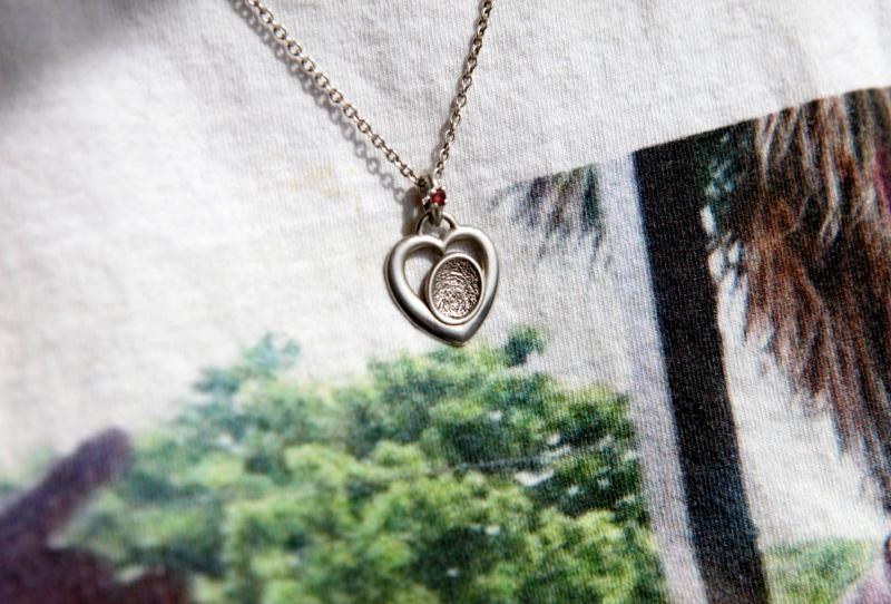 Sue Kruczek wears a pendant with the fingerprint of her son, Nick, who died of an opioid overdose.
