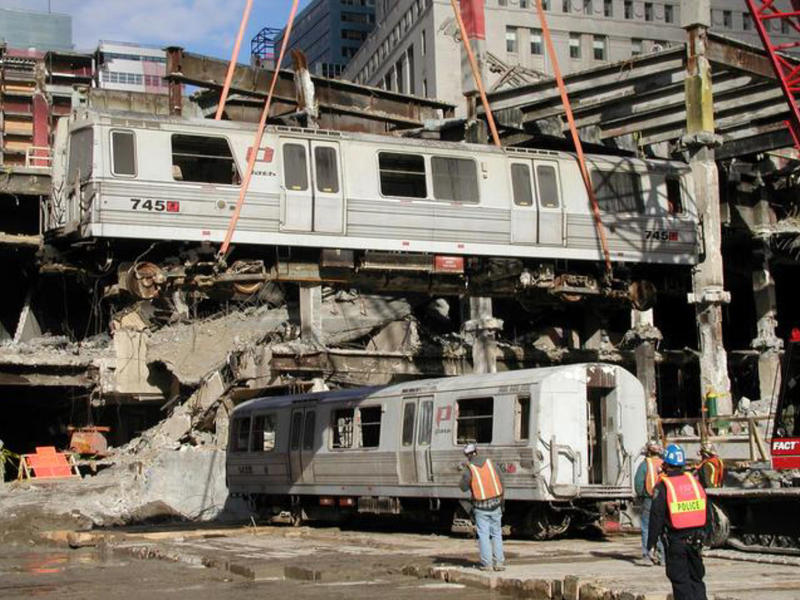 During recovery from the World Trade Center wreckage, Car 745 is swung over Car 143 by crane.