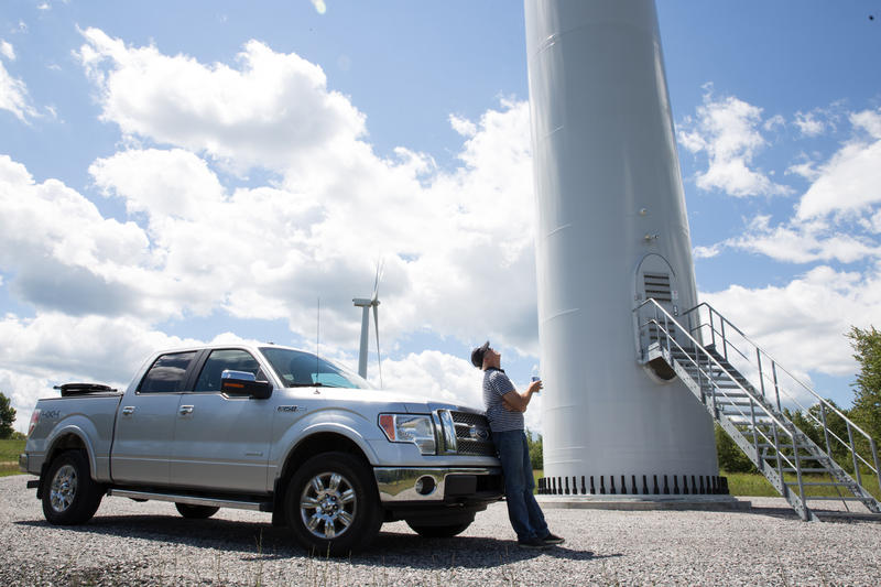 BNE Energy CEO Greg Zupkus looks up at one of his company's wind turbines in Colebrook. The wind farm has been operational for nearly a year.