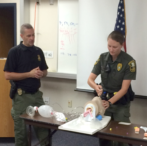 State Trooper Robert Lanquette, trainer, with EnCon Officer Alexandra Blackwell, practicing the administration of Narcan.