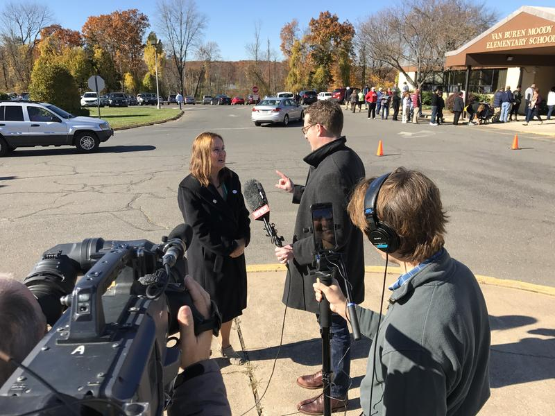 WNPR reporter Jeff Cohen talks with Connecticut Secretary of the State Denise Merrill outside Moody Elementary School in Middletown, Connecticut.