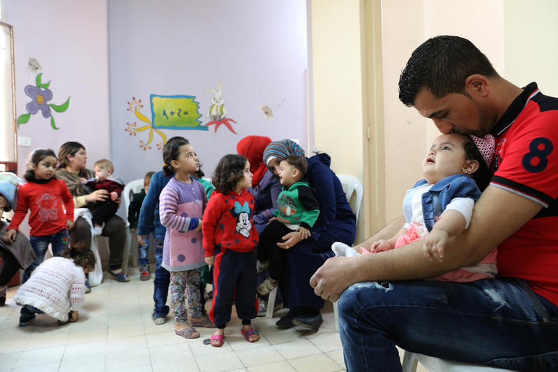Ali Radi kisses his daughter, Cham, while waiting with other Syrian refugees to see a nurse at the Howard Karagheusian primary health care center, in Beirut, Lebanon early in 2016.