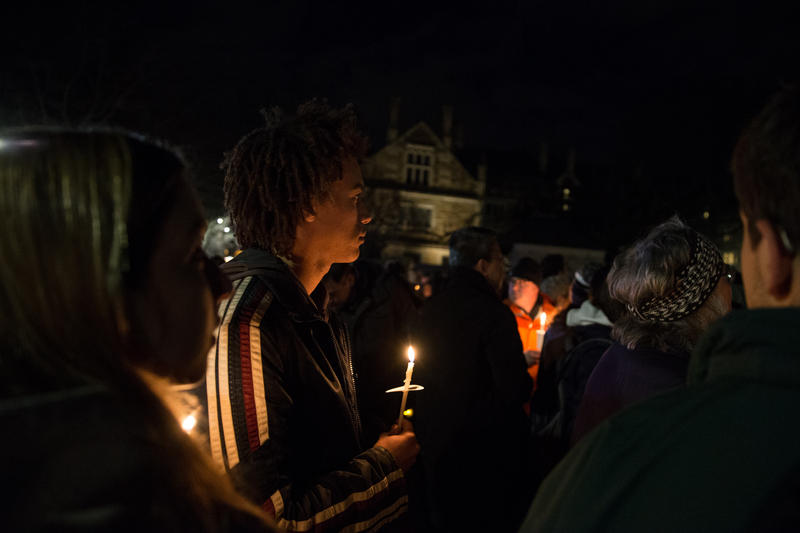 Kai Nugent (center) holds a candle at the Yale vigil Sunday night. He says he has friends who have been afraid that their families won't be able to be in the United States.